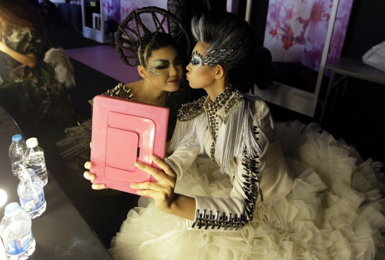 Models use an iPad to take a photo backstage before the MGPIN collection show by Maogeping Image Design Art School at China Fashion Week in Beijing. (Jason Lee/Reuters)
