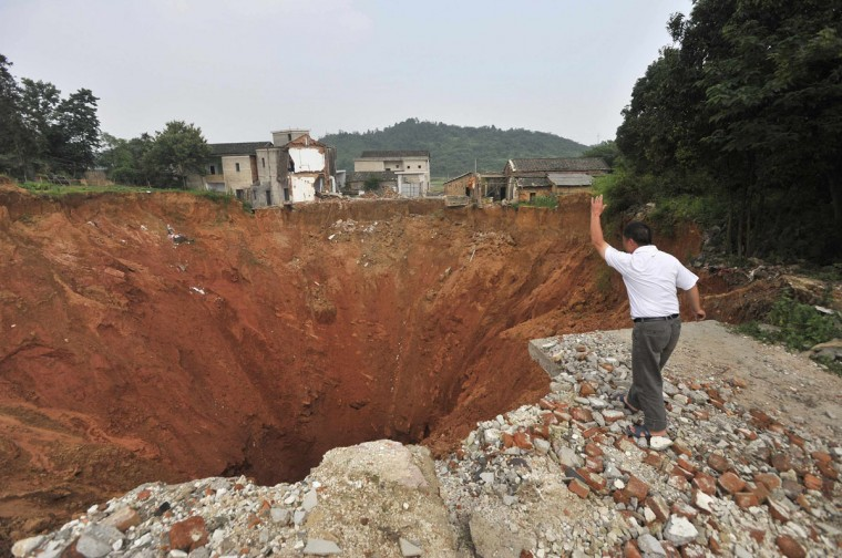 A local resident throws a stone into a sinkhole near Qingquan primary school in Dachegnqiao town of Ningxiang, Hunan province on June 15, 2010. The hole, 150 meters (492 feet) wide and 50 meters (164 feet) deep, has been growing since it first appeared in January and had destroyed 20 houses when this picture was taken. (Stringer/Reuters Photo)