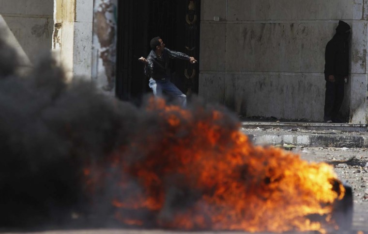 A protester, opposing Egyptian President Mohamed Mursi, throws a stone at riot police, near a fire, during clashes in front of Security Directorate in Port Said city, 105 miles northeast of Cairo March 5, 2013. Police shot into the air and fired tear gas during clashes with hundreds of protesters in Egypt's Port Said on Tuesday, the third day of violent protests in the port city, a Reuters witness said. (Amr Abdallah Dalsh/Reuters)