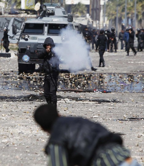 A riot policeman releases tear gas at protesters opposing Egyptian President Mohamed Mursi during clashes in front of Security Directorate in Port Said city, 105 miles northeast of Cairo March 5, 2013. Police shot into the air and fired tear gas during clashes with hundreds of protesters in Egypt's Port Said on Tuesday, the third day of violent protests in the port city, a Reuters witness said. Waves of demonstrations have been erupting in Port Said since January after the detention of dozens of people in connection with a football riot last year when 70 died. (Amr Abdallah Dalsh/Reuters)