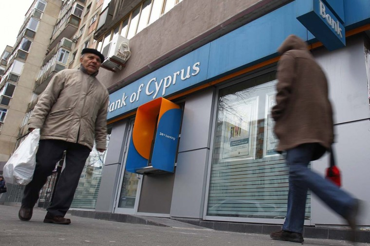 People walk past a branch of Bank of Cyprus in Bucharest March 25, 2013. Cyprus clinched a last-ditch deal with international lenders to shut down its second largest bank and inflict heavy losses on uninsured depositors, including wealthy Russians, in return for a 10 billion euro ($13 billion) bailout. (Bogdan Cristel/Reuters)