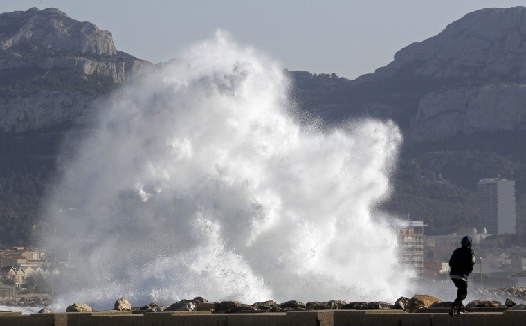 A passer-by walks as a high wave hits the waterfront in Marseille March 14, 2013. French public weather agency Meteo France issued an orange alert warning of winds threatening southern French departments. (Jean-Paul Pelissier/Reuters photo)