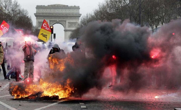 Employees of PSA Peugeot Citroen burn tyres during a demonstration in front of the Peugeot headquarters near the Arc de Triomphe in Paris March 18, 2013 to protest against the closure of the PSA Aulnay automobile plant and the government's economic policy and industrial layoffs. (Jacky Naegelen/Reuters)