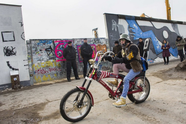 A man on a chopper-style bicycle rides past the entrance to a construction site for luxury apartments at a 0.8 mile section of the former Berlin Wall, also known as the East Side Gallery, in Berlin. Four segments of the wall were removed on Wednesday morning, almost a month after builders had stopped tearing down the wall due to protests. Developers plan to build luxury apartments close to the East Side Gallery, which is adorned with the work of artists such as Keith Haring and Gerald Scarfe. (Thomas Peter/Reuters)