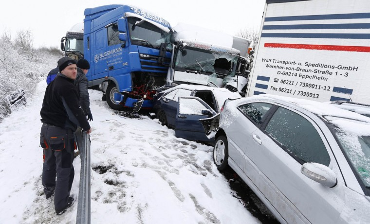 Truck drivers who were involved in an accident, stand next the wreckage of vehicles on highway A45 between Giessen and Hanau near the city of Woelfersheim. More than 100 vehicles were involved in a multiple pile-up on Tuesday after they crashed on the snowy highway, police at the scene said. Several people were injured in the incident. (Kai Pfaffenbach/Reuters)
