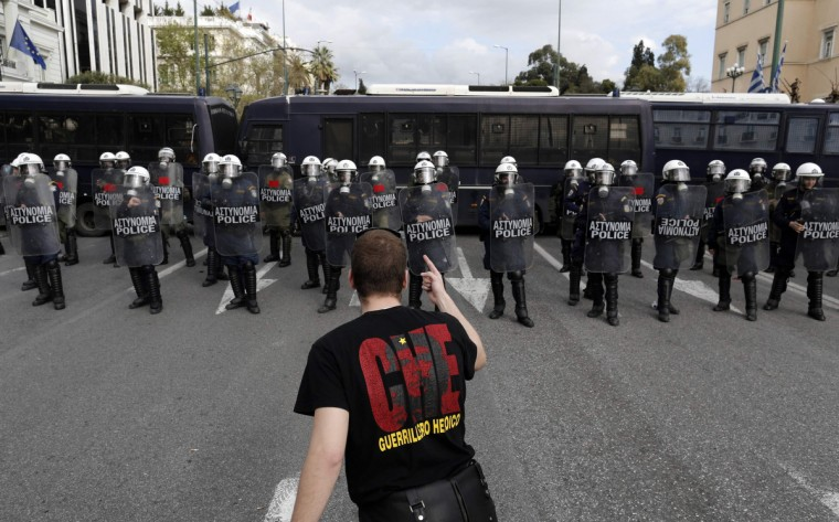 A university student confronts riot policemen during a rally against a planned overhaul of the Greek university system outside the parliament in Athens. (John Kolesidis/Reuters photo)