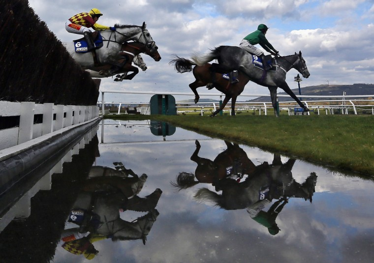 Horses jump a fence during the Novices' Steeple Chase race at the Cheltenham Festival horse racing meet in Gloucestershire, western England. (Stefan Wermuth/Reuters photo)
