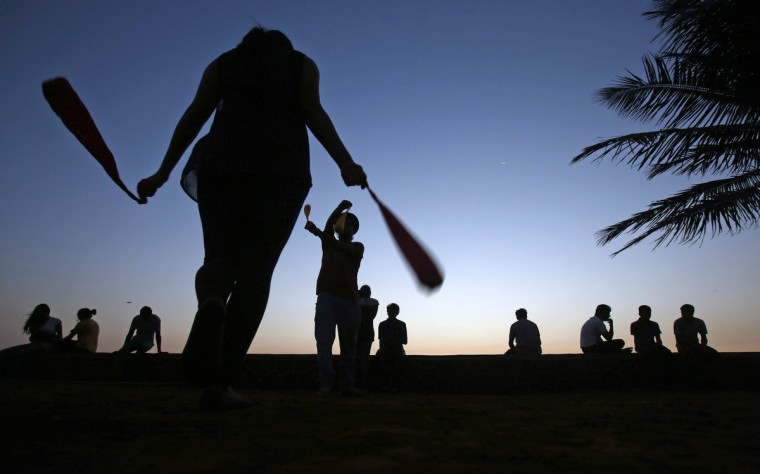 """Naina (L), a student, and her instructor Rahul practice swinging """"pois"""" at a park in Mumbai. Poi is a recreational activity in which people swing weights tied to strings in a variety of patterns and shapes, the instructor said. (Vivek Prakash/Reuters photo)"""