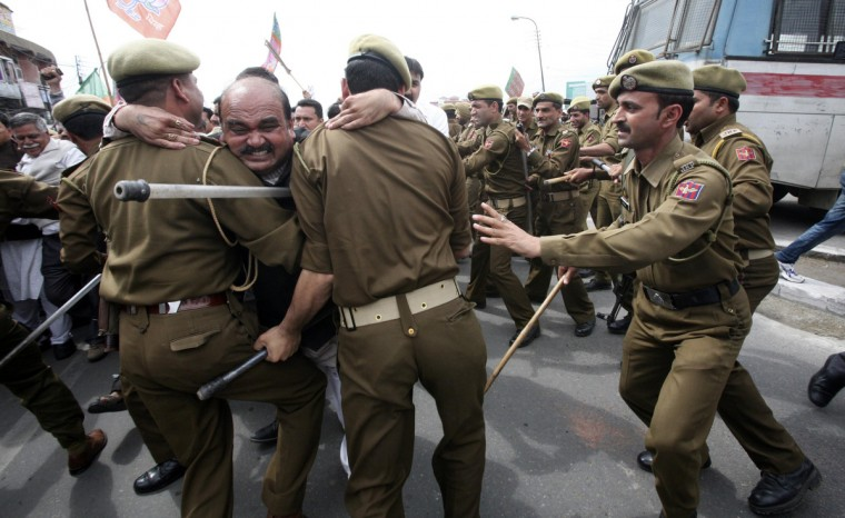 An activist from India's main opposition Bharatiya Janata Party (BJP) scuffles with police during a protest in Jammu. Hundreds of the BJP activists on Thursday held a protest in Jammu against the killing of five Central Reserve Police Force (CRPF) personnel. Two militants hiding automatic rifles and grenades in cricket kit opened fire on a paramilitary camp on the Indian side of Kashmir on Wednesday, killing five CRPF personnel and wounding five, police said. (Mukesh Gupta/Reuters photo)