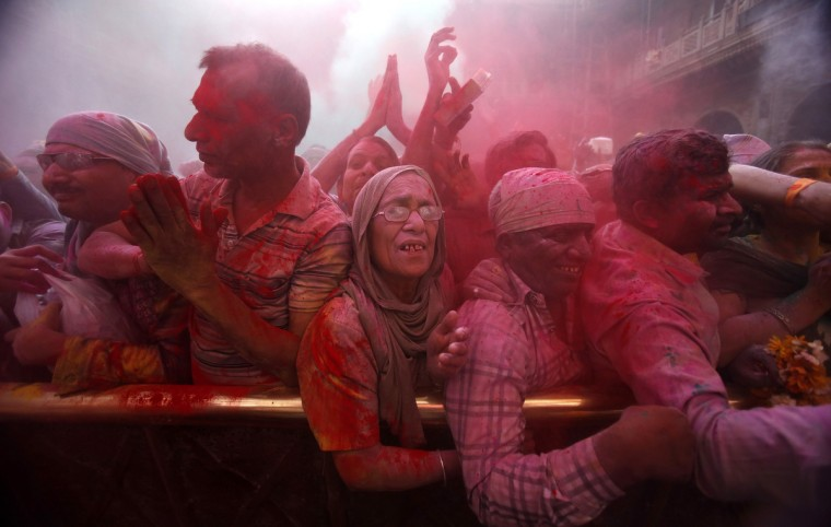 Hindu devotees stand amid a cloud of red colored powder during Holi celebrations at the Bankey Bihari temple in Vrindavan in the northern Indian state of Uttar Pradesh. Holi, also known as the Festival of Colors, heralds the beginning of spring and is celebrated all over India. (Vivek Prakash/Reuters)