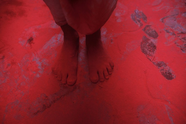 The feet of a man covered in red coloured powder are pictured during Holi celebrations in a lane near the Bankey Bihari temple in Vrindavan in the northern Indian state of Uttar Pradesh. Holi, also known as the Festival of Colours, heralds the beginning of spring and is celebrated all over India. (Vivek Prakash/Reuters)