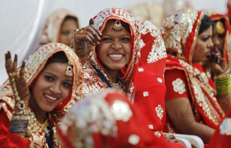 Muslim brides smile as they wait for the start of their rituals during a mass marriage ceremony in the western Indian city of Ahmedabad March 3, 2013. A total of 162 Muslim couples from the across the Gujarat state took wedding vows on Sunday during the mass wedding ceremony organised by a Muslim voluntary organisation, organisers said. (Amit Dave/Reuters)