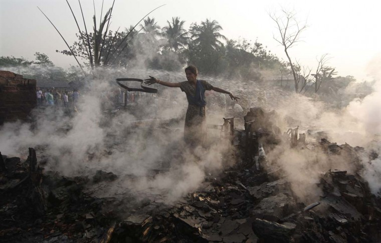 A slum dweller throws her belongings amid the remains of her hut that was burnt in a fire which broke out in a slum area on the outskirts of Kolkata March 16, 2013. Hundreds of huts were burnt in a fire early Saturday morning, and no injuries or casualties were reported, local media reported. (Rupak De Chowdhuri/Reuters)