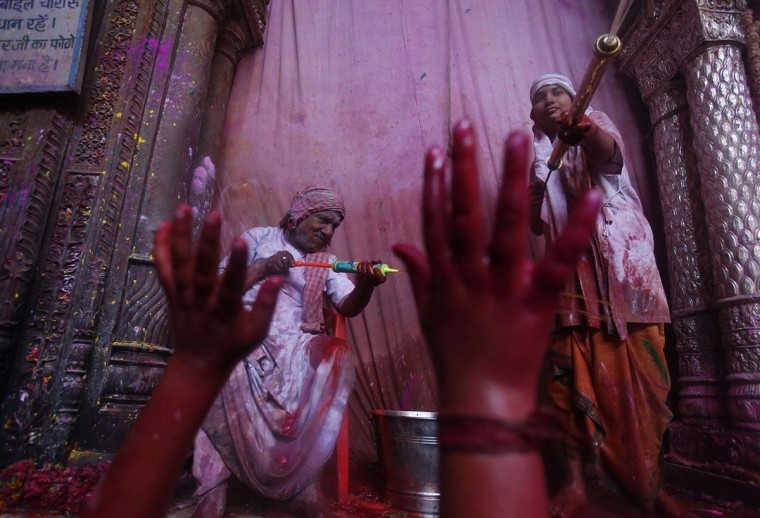 Hindu priests spray colored water on devotees during holi celebrations at the Bankey Bihari temple in Vrindavan in the northern Indian state of Uttar Pradesh March 25, 2013. Holi, also known as the Festival of Colors, heralds the beginning of spring and is celebrated all over India. (Vivek Prakash/Reuters)