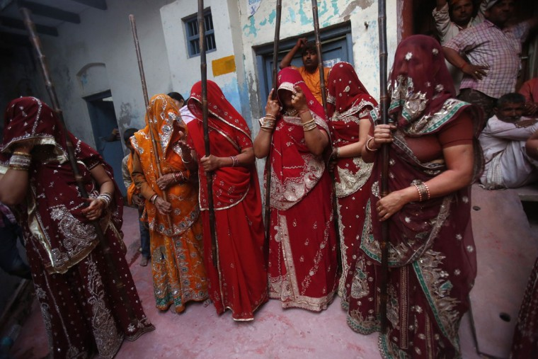 "A group of women stand while holding sticks during Lathmar Holi at the village of Barsana in the northern Indian state of Uttar Pradesh. In a Holi tradition unique to Barsana and Nandgaon villages, men sing provocative songs to gain the attention of women, who then ""beat"" them with bamboo sticks called ""lathis"". (Vivek Prakash/Reuters)"