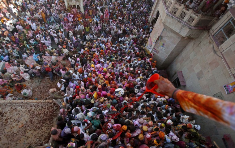 A Hindu devotee pours colored water on people entering a temple during Lathmar Holi at the village of Barsana in the northern Indian state of Uttar Pradesh on March 21, 2013. (Vivek Prakash/Reuters)