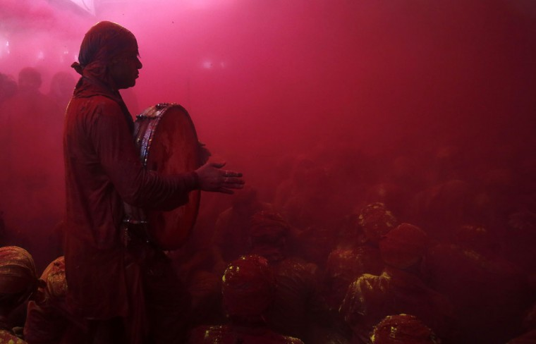 "A Hindu devotee plays a drum in a cloud of colored powder inside a temple during Lathmar Holi at the village of Barsana in the northern Indian state of Uttar Pradesh. In a Holi tradition unique to Barsana and Nandgaon villages, men sing provocative songs to gain the attention of women, who then ""beat"" them with bamboo sticks called ""lathis."" Holi, also known as the Festival of Colors, heralds the beginning of spring and is celebrated all over India. (Vivek Prakash/Reuters)"