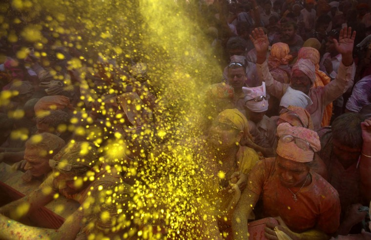 Hindu devotees throw colored powder at a temple during Lathmar Holi at the village of Barsana in the northern Indian state of Uttar Pradesh. (Vivek Prakash/Reuters)