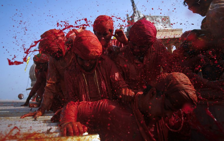 "Hindu devotees throw colored water at each other at a temple during Lathmar Holi at the village of Barsana in the northern Indian state of Uttar Pradesh March 21, 2013. In a Holi tradition unique to Barsana and Nandgaon villages, men sing provocative songs to gain the attention of women, who then ""beat"" them with bamboo sticks called ""lathis"". Holi, also known as the Festival of Colors, heralds the beginning of spring and is celebrated all over India. (Vivek Prakash/Reuters)"