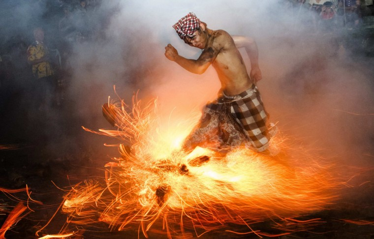"""A Balinese man kicks up fire during the """"Perang Api"""" ritual ahead of Nyepi day, which falls on Tuesday in Gianyar on the Indonesian island of Bali. Nyepi is a day of silence for self-reflection to celebrate the Balinese Hindu new year, where Hindus in Bali observe meditation and fasting, but are not allowed to work, cook, light lamps or conduct any other activities. (Reuters)"""