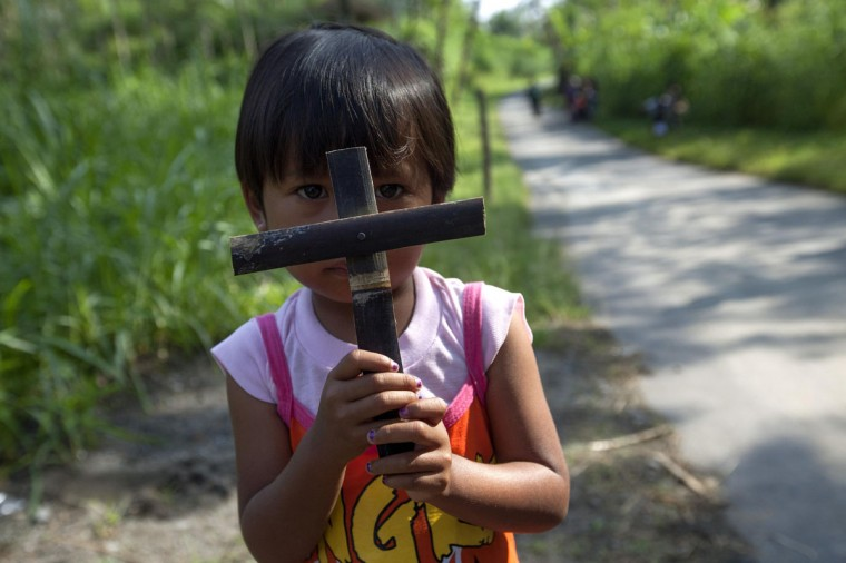 March 29, 2013: A child holds up a cross made of bamboo during the celebration of Holy Week on Good Friday at Gantang Village near Magelang, in the province of Central Java, Indonesia. (Dwi Oblo/Reuters)