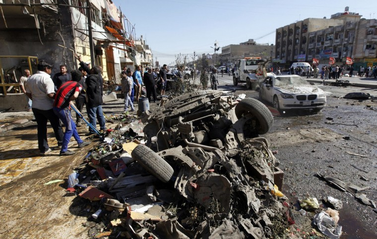 Residents gather at the site of a car bomb attack in the AL-Mashtal district in Baghdad March 19, 2013. A series of coordinated car bombs and blasts hit Shi'ite districts across Baghdad and south of the Iraqi capital on Tuesday, killing at least 25 people on the tenth anniversary of the U.S.-led invasion.(Mohammed Ameen/Reuters photo)
