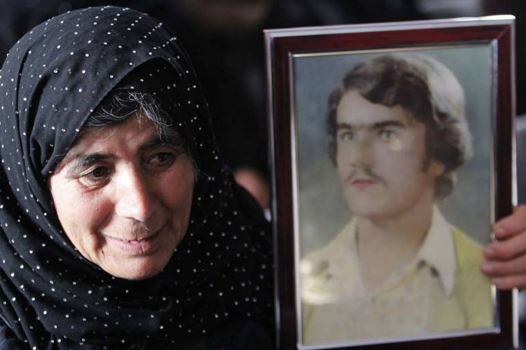 A woman holds a picture of her son, who was one of the victims of the 1988 chemical attack, as she attends a ceremony commemorating the victims in the Kurdish town of Halabja, near Sulaimaniya, 160 miles northeast of Baghdad, March 16, 2013. Iraqi Kurds on Saturday marked the 25th anniversary of the chemical attack on the northern Iraqi city of Halabja by Saddam Hussein's forces. Up to 5,000 people may have been killed by chemical gas, villages were razed and thousands of Kurds were forced into camps during the 1988 Anfal genocidal campaign against Iraqi Kurds. (Thaier al-Sudani/Reuters)