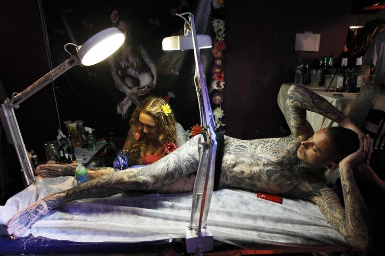 A tattoo artist works on the leg of a client at the Israel Body Art Society Festival in a Tel Aviv club March 16, 2013. (Amir Cohen/Reuters)