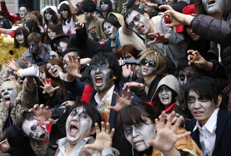 People, dressed as zombies, pose for photos after the Roppongi Zombie Walk in Tokyo March 31, 2013. About 50 people dressed up as zombies early evening on Sunday, catching the attention of pedestrians on the streets of Tokyo's downtown Roppongi district. (Yuya Shino/Reuters)