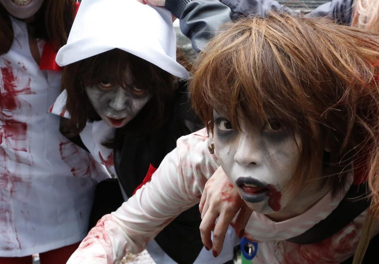 People, dressed as zombies, participate in the Roppongi Zombie Walk in Tokyo March 31, 2013. About 50 people dressed up as zombies early evening on Sunday, catching the attention of pedestrians on the streets of Tokyo's downtown Roppongi district. (Yuya Shino/Reuters)
