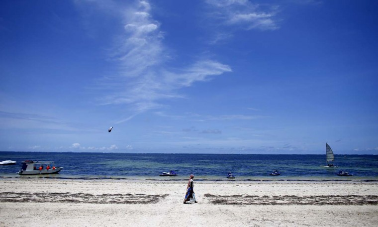 A woman walks by the beach of Kenya's coastal city of Mombasa March 6, 2013. (Marko Djurica/Reuters)
