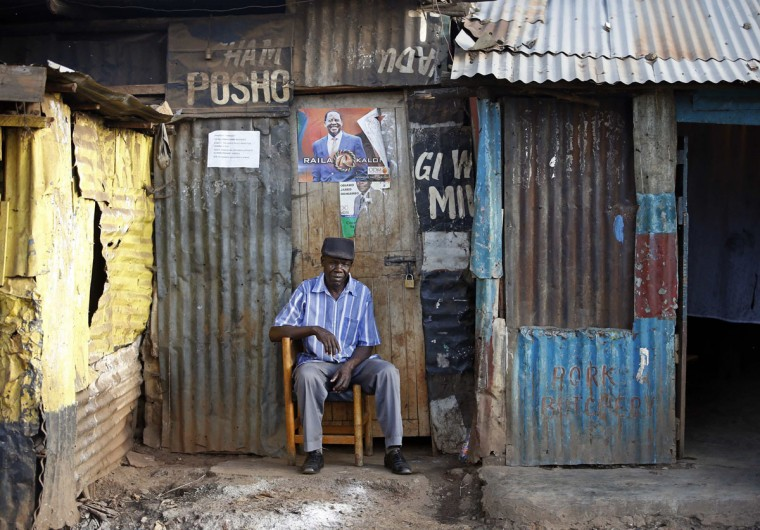 A supporter of Kenyan Prime Minister Raila Odinga sits in front of a poster outside his house as he waits for election results in the Kibera slum in Nairobi March 8, 2013. Kenya said it was determined to complete the count on Friday in a tight presidential race that has put Uhuru Kenyatta ahead of his main rival Prime Minister Raila Odinga and in with a chance of outright victory. (Goran Tomasevic/Reuters)