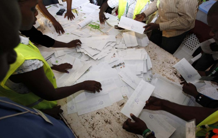 Officials from the Independent Electoral and Boundaries Commission (IEBC) sort out ballot papers after voting closes for presidential and parliamentary elections in Kisumu, 218 miles west of the capital Nairobi, March 4, 2013. (Thomas Mukoya/Reuters)