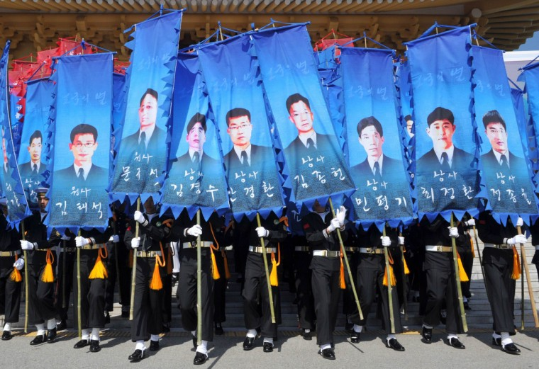 South Korean honor guards hold banners with pictures of the sailors who died in the sinking of a South Korean naval vessel by what Seoul insists was a North Korean submarine, during an event marking the third anniversary of the incident, at the national cemetery in Daejeon. 46 sailors died when the Cheonan corvette sunk. (Kim Jae-Hwan/Pool)