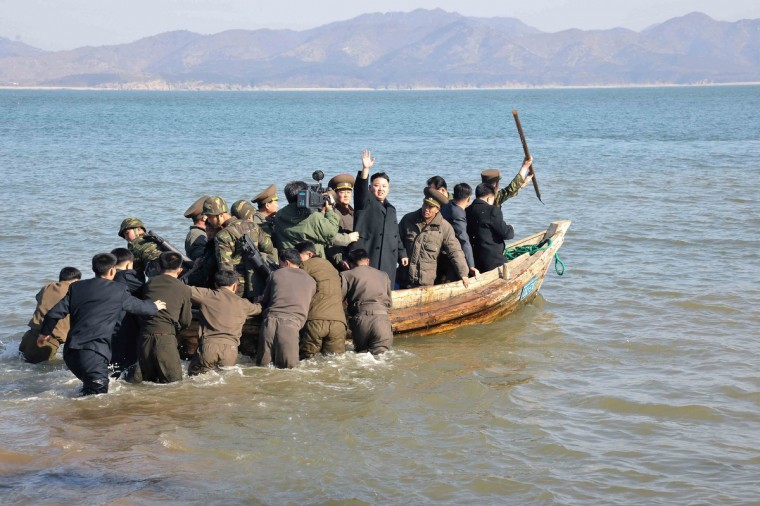 North Korean leader Kim Jong-Un (C) waves while in a boat during his visit to the Wolnae Islet Defence Detachment in the western sector of the front line, which is near Baengnyeong Island of South Korea. South Korea and U.S. forces are conducting large-scale military drills, while the North is also gearing up for a massive military exercise. North Korea has accused the U.S. of using the military drills in the South as a launch pad for a nuclear war and has said to scrap the armistice with the U.S. that ended the 1950-53 Korean War. (KCNA via Reuters)