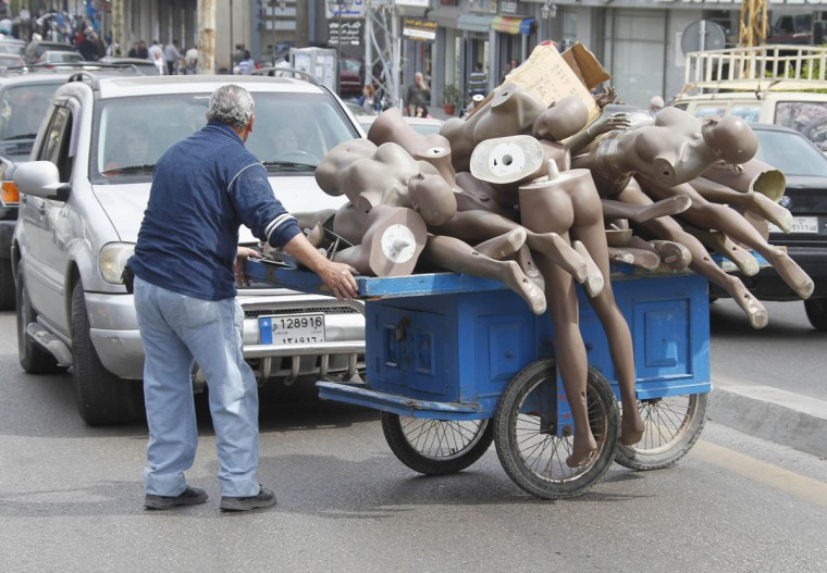 A man pushes a cart filled with mannequins in Sidon, Lebanon. (Ali Hashisho/Reuters)