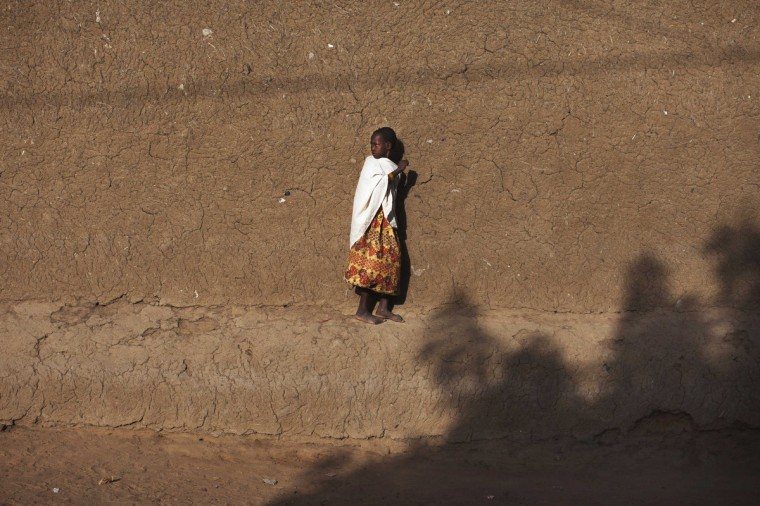 A girl walks on the ledge of a mud brick house in Gao. (Joe Penney/Reuters)