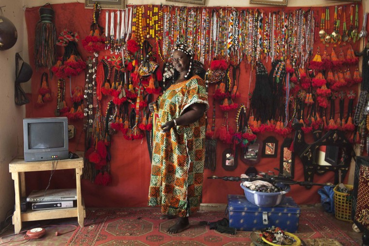 Hally Bara, an artisan, poses for a picture in front of traditional Songhai and Tuareg headdresses and jewelry she made at the store in her house in Gao, Mali, March 6, 2013. (Joe Penney/Reuters Photo)