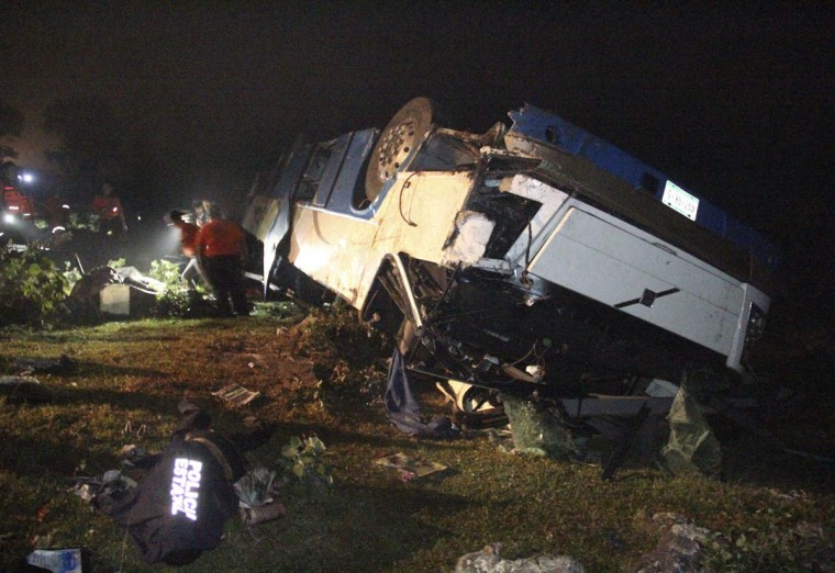 People stand near a covered body lying next to the wreckage of a passenger bus after it collided with a car near the town of Naolinco, in the western Mexican state of Veracruz March 30, 2013. At least 12 people died when the bus and the car collided in a mountainous part of Veracruz on Saturday evening, local emergency services said. The accident near the town of Naolinco sent the bus tumbling down a slope some 650-1000 feet, and left at least 15 passengers injured, a local official said. (Stringer/Stringer)