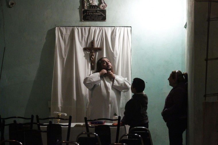 Catholic priest Adolfo Huerta gets ready before conducting a mass outside a house in a neighbourhood in Saltillo February 26, 2013. (Daniel Becerril/Reuters)