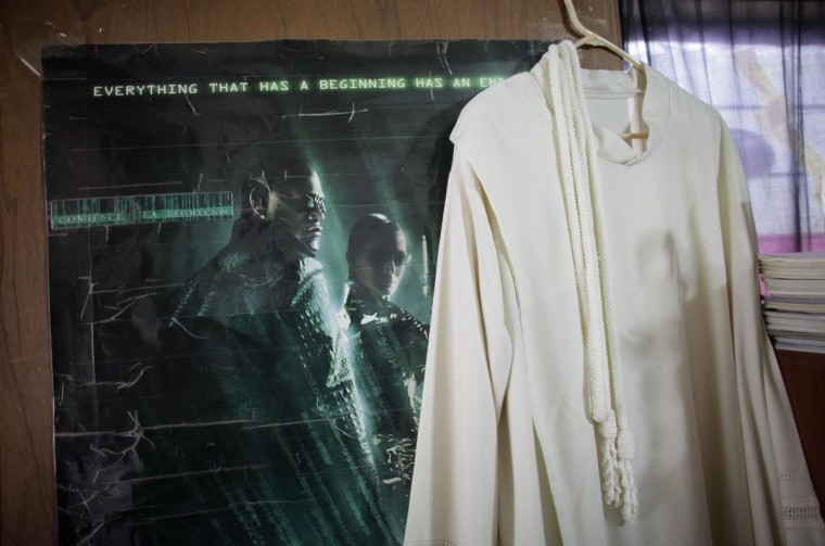 The robe of Catholic priest Adolfo Huerta hangs next to a poster of the movie Matrix in Saltillo February 22, 2013. (Daniel Becerril/Reuters)