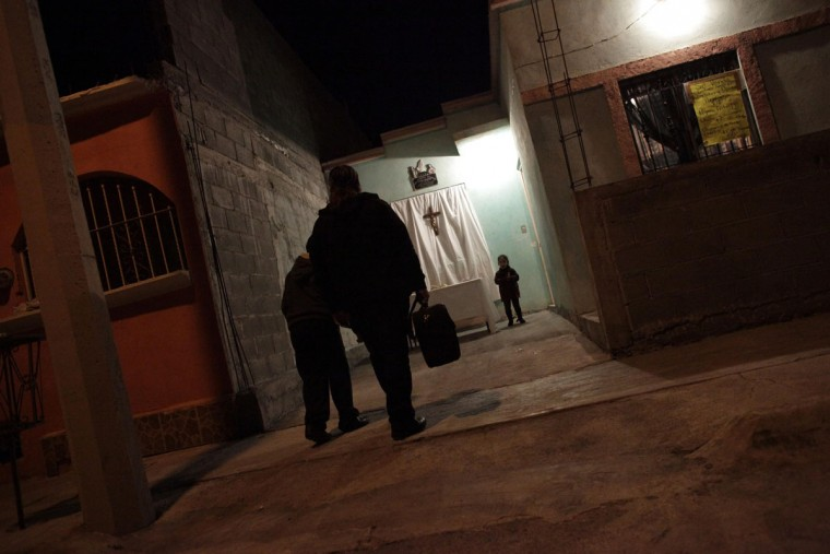 Catholic priest Adolfo Huerta walks with a child to a place between two houses where he will conduct mass in Saltillo February 26, 2013. (Daniel Becerril/Reuters)