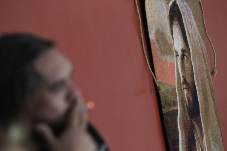 Catholic priest Adolfo Huerta smokes a cigarette while standing next to a painting of Jesus Christ in Saltillo February 22, 2013. (Daniel Becerril/Reuters)