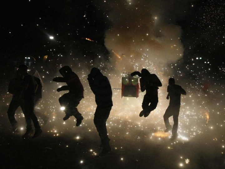 """Residents are showered in sparks as fireworks explode during the annual event """"Quema de toritos"""" (Burning of the bulls) in the municipality of Tultepec near Mexico City March 8, 2013. According to the organizer, the fireworks are dedicated to Saint John of God, the patron saint of pyrotechnics in Tultepec, a city renowned for producing traditional fireworks. Picture taken March 8, 2013. (Bernardo Montoya/Reuters)"""