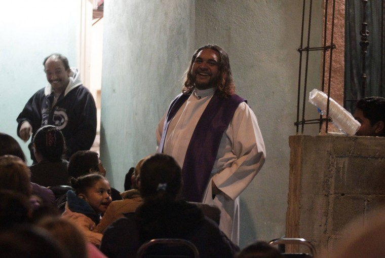 Catholic priest Adolfo Huerta laughs while conducting a mass outside a house in a neighbourhood in Saltillo February 26, 2013. (Daniel Becerril/Reuters)