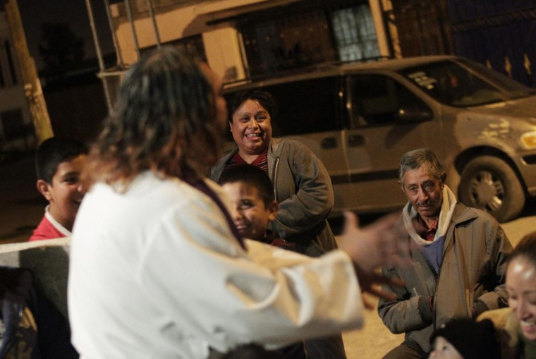 People laugh as Catholic priest Adolfo Huerta conducts a mass outside a house in a neighbourhood in Saltillo February 26, 2013. (Daniel Becerril/Reuters)