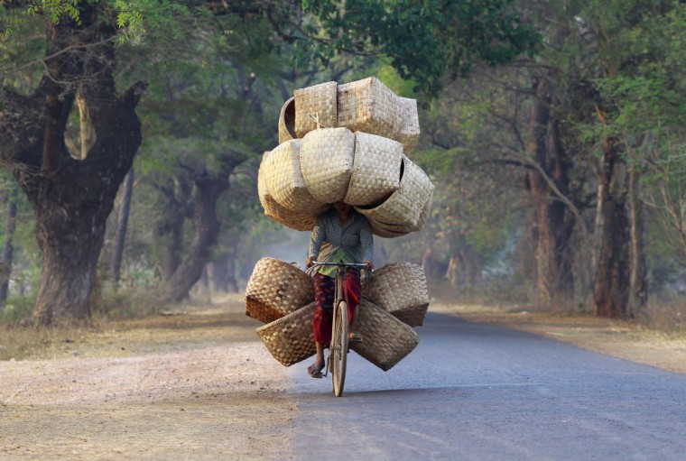 A woman cycles as she carries baskets to sell in a market near Lapdaung mountain in Sarlingyi township. (Soe Zeya Tun/Reuters)