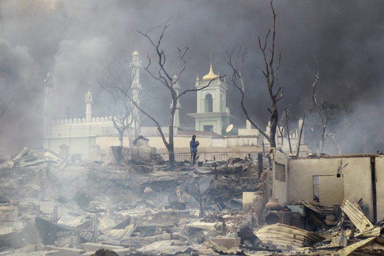 A man stands in front of a mosque as it burns in Meikhtila. The central Myanmar town declared a curfew for a second night on Thursday after clashes killed 10 people, including a Buddhist monk, and injured at least 20, authorities said. Riots erupted in Meikhtila, 540 km (336 miles) north of Yangon, on Wednesday after an argument between a Buddhist couple and the Muslim owners of a gold shop escalated into a riot involving hundreds of people, police said. (Soe Zeya Tun/Reuters)