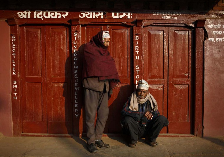 Men bask in the sun outside a closed shop at the ancient city of Bhaktapur near Nepal's capital Kathmandu March 18, 2013. (Navesh Chitrakar/Reuters)