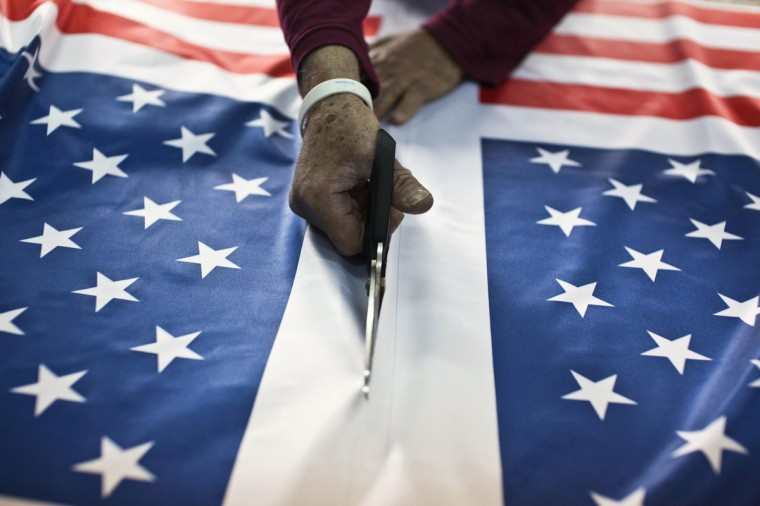 A worker at a factory in Kfar Saba near Tel Aviv cuts fabric printed with U.S. flags ordered ahead of President Barack Obama's visit to Israel. It was the most work the factory has had since Egyptian President Anwar Sadat visited Israel in 1977, owner Avi Marom said on Tuesday. The White House has yet to officially announce the dates for the trip, but Israeli news media have reported that Obama will arrive in Israel on March 20. (Nir Elias/Reuters)
